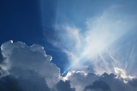 Schöne Wolkenfedern gegen den blauen Himmel, geweiht von der Sonne, Hintergrund für Design.