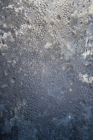 Winter background, frozen raindrops on the glass from the strong frost and wind the texture of ice on the window.