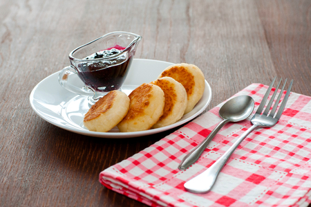 Cheese pancakes with jam, on a white plate with a fork, a teaspoon and a napkin horizontal format, side view