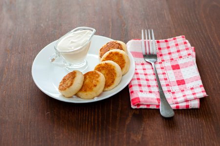 Cheese pancakes with sour cream on a white plate on pink napkin with a fork. Can be used for menu design.