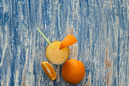 Cocktail from fresh orange juice on a blue wooden background, copy space closeup, flat lay