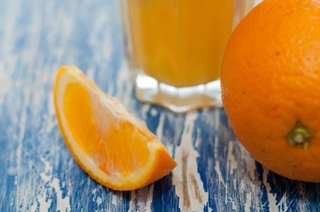 Orange and glass of juice on a blue wooden background