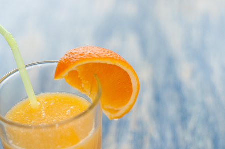 Alcoholic cocktail of fresh orange juice on a blue wooden background, copy space closeup