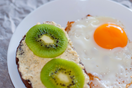 Healthy and tasty breakfast, wholemeal bread sandwich with kiwi and a fried egg on a white plate, close-up top view