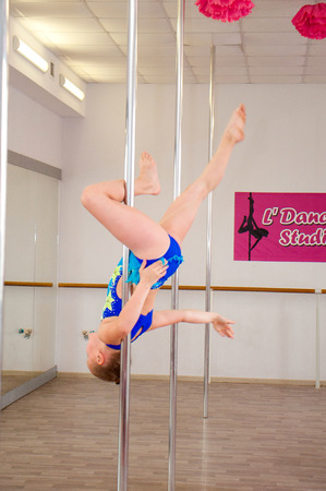 Chernigov, Ukraine, May 25, 2019: pole dance competitions in a dance studio. Very beautiful athletic girl in a blue bathing suit dancing on a pole Editorial