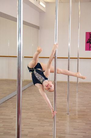 Chernigov, Ukraine, May 25, 2019: pole dance competitions in a dance studio. Very beautiful athletic girl in a black bathing suit dancing on a pole
