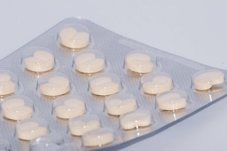Heart, pills in pack on white background
