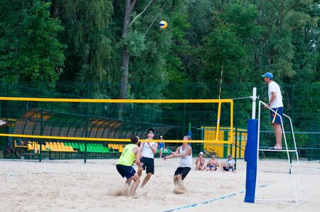 Ukraine, Chernigov, June 9, 2019: Beach Volleyball Championship of the city. Beautiful young sports strong men play volleyball on the city beach, in the summer in sunny hot weather.