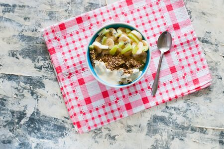 Granola with Greek yogurt kiwi and banana in a bowl with a spoon on a pink napkin, view from the top, flat lay. Fitness diet for weight loss, proper and tasty food