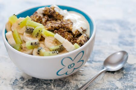 Granola, kiwi, banana and greek yogurt in a bowl, a plate with a spoon on a gray concrete background. Fitness diet for weight loss and proper nutrition