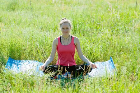 Young beautiful woman doing yoga on nature in summer. Slender girl meditates on a sunny morning.