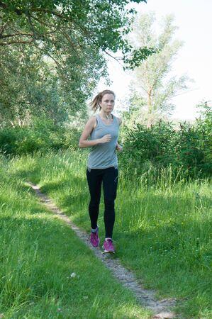 Schöne, sportliche, schlanke Frau mit Kopfhörern und Sportanzug läuft durch den Park, Sommer, sonniger Morgen. Morgens Joggen und Sport
