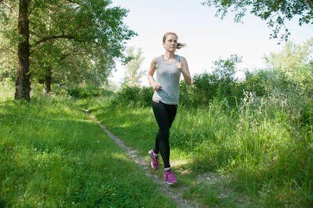 Mujer hermosa, atlética y esbelta con auriculares y un traje deportivo corre por el parque, verano, mañana soleada. Trotar y deportes matutinos Foto de archivo