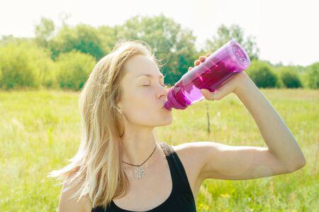 Mujer joven con una figura deportiva, cuerpo, delgado, después de un entrenamiento bebe agua de una botella