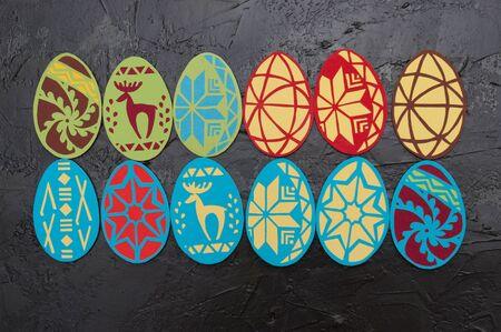 Handmade magnets in the shape of Easter eggs on a dark gray concrete background, Ukrainian traditional symbols, copy space holiday card