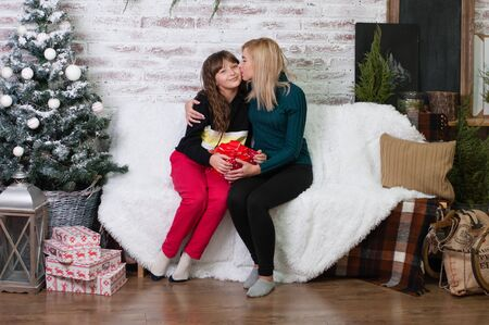 Teen girl gives a gift to her mother near the New Year tree Standard-Bild - 131770364