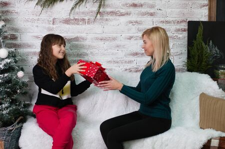 Teen girl gives a gift to her mother near the New Year tree Standard-Bild - 131770365