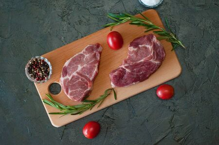 Flat lay, raw meat steaks, pork, peppers, rosemary, sea salt and tomatoes on a cutting board, on a dark gray concrete background Standard-Bild - 131770535
