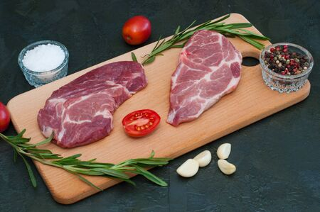 Pork, raw steaks and spices, garlic, salt, pepper, tomatoes and rosemary on a cutting board Standard-Bild - 131770539
