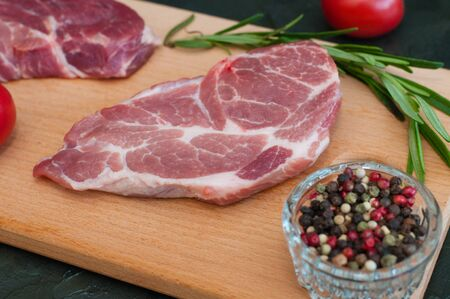 Raw pork steaks, rosemary, tomatoes and peppers on a wooden cutting board, dark background, side view Standard-Bild - 131770541