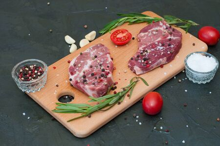 Raw meat on a cutting board, sprinkled with salt and pepper, garlic, rosemary and tomato, top view and side view Standard-Bild - 131775507