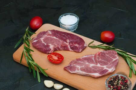 Pork, raw steaks and spices, garlic, salt, pepper, tomatoes and rosemary on a cutting board Standard-Bild - 131775510
