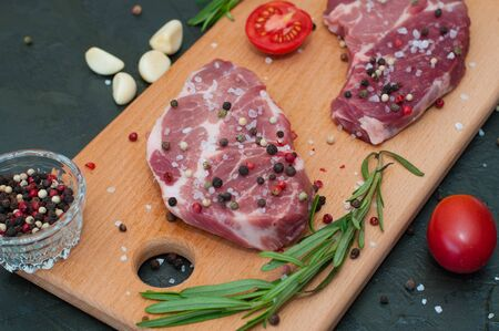 Raw meat on a cutting board, sprinkled with salt and pepper, garlic, rosemary and tomato, top view and side view Standard-Bild - 131775508