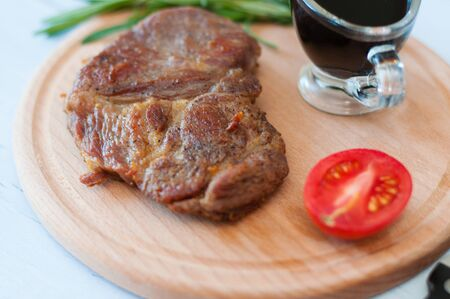 Cooked grilled pork steak on a wooden round board, with soy sauce, rosemary and tomato Standard-Bild - 131775509
