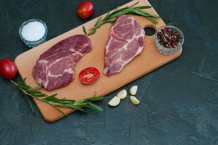 Flat lay, pork, raw steaks and spices, garlic, salt, pepper, sliced tomatoes and rosemary on a cutting board Standard-Bild - 131775511