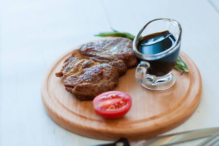 Cooked, grilled pork steak on a wooden round board, with soy sauce, rosemary and tomato, on a light background with copy space Standard-Bild - 131775516