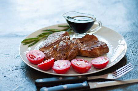 Fragrant, juicy meat steaks of veal, beef or pork with rosemary, tomatoes and sauce, on a gray plate, on a dark concrete background Standard-Bild - 131775514
