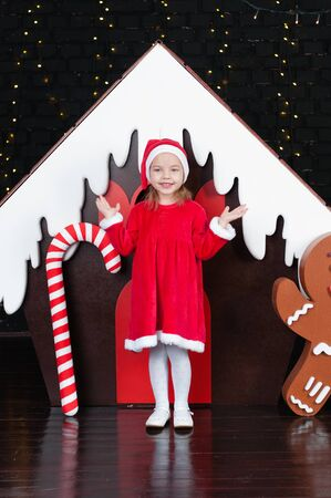 Cheerful child girl in a red dress near the New Year tree and gingerbread house Standard-Bild - 131269653