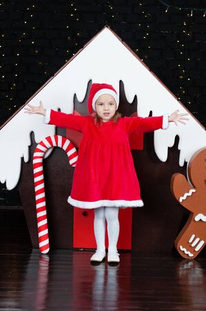 Cheerful child girl in a red dress near the New Year tree and gingerbread house Standard-Bild - 131269657
