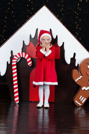 Very beautiful baby girl in a red dress is dreaming near the Christmas gingerbread house sends an air kiss Standard-Bild - 131269659