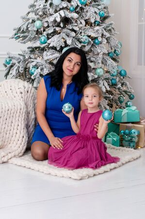 Young woman mother and little girl playing having fun with Christmas balls near the Christmas tree. Standard-Bild - 131209479