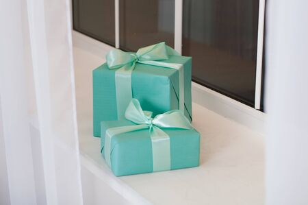 Christmas, New Year festive background of the boxes with gifts in turquoise colors on the white window sill Standard-Bild - 131209568