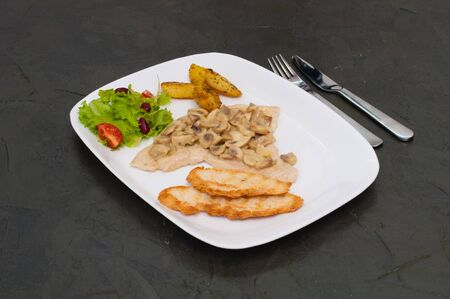 Braised champignons with fish fillet, salad fried potatoes and croutons Standard-Bild - 132275308