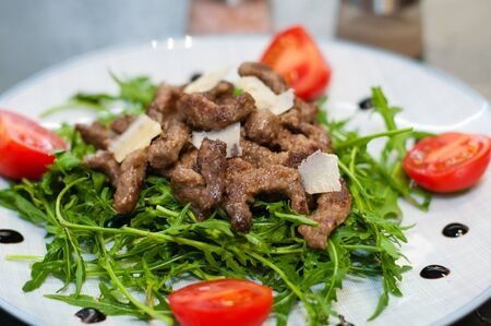 Tasty and juicy grilled meat arugula, cheese, tomato sauce and spices Standard-Bild - 131669526