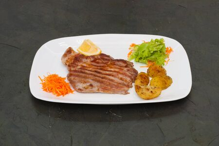 Juicy grilled meat steak with lemon, carrots lettuce and potatoes. Standard-Bild - 131670095