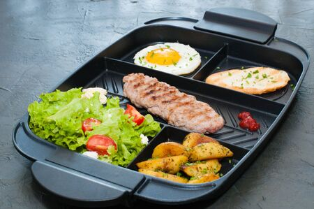 Breakfast, cutlet or steak, tomato salad, fried potatoes, croutons and fried egg on a black plate. Restaurant serving lunch. Standard-Bild - 131674637