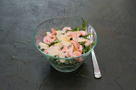 Salad with shrimp, arugula and cheese in a glass bowl or plate, fork dark background Standard-Bild - 131675360