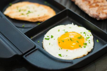 Lunch, grilled steak or cutlet, toast and egg on a black plate. The concept of a healthy diet, diet, menu. Place for text with left, copy space. Standard-Bild - 131675104