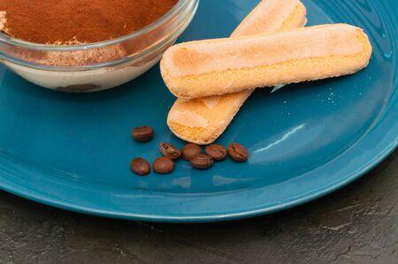 Savoyardi cookies with tiramisu italian dessert in a glass bowl on a blue plate Standard-Bild - 131675015