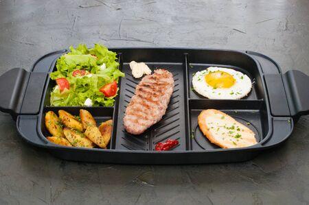 Colazione, cotoletta o bistecca, insalata di pomodori, crostino di patate fritte e uovo al tegamino