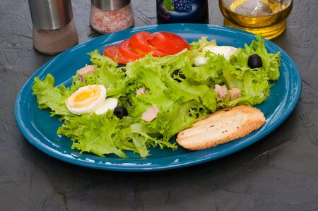 Salad with tuna, eggs, tomato, olives, spices and croutons, sauce or oil on a blue plate, close-up. Standard-Bild - 131674601