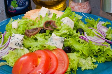 Salad with octopus or squid, cheese, tomato, olives, onions, spices and croutons, sauce or butter on a blue plate Standard-Bild - 131674408