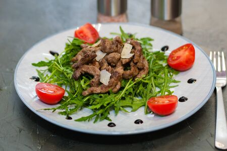 Tasty and juicy grilled meat arugula, cheese, tomato sauce and spices Standard-Bild - 131676093