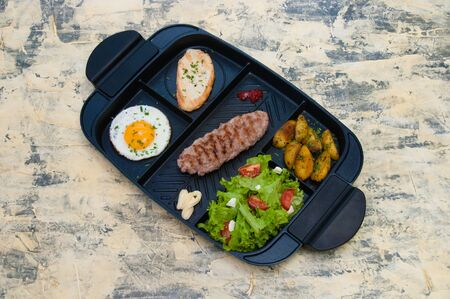 Breakfast, fried steak or cutlet, salad with tomato and green vegetables, toast, potato, egg top view, light background. The concept of a healthy diet, diet, menu, good nutrition.
