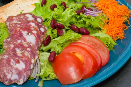 Salad with sausage, tomatoes, beans carrots, spices, olive oil or sauce. Restaurant serving Italian food Standard-Bild - 131679736