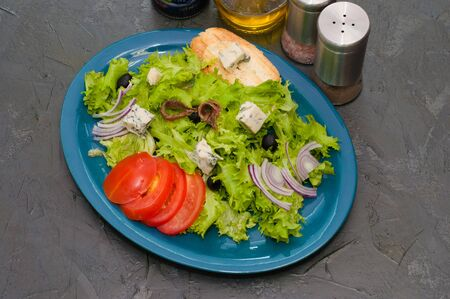 Salad with octopus or squid, cheese, tomato, olives, onions, spices and croutons, sauce or butter on a blue plate, copy space.
